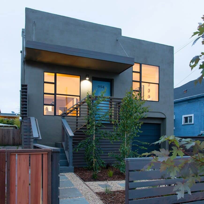 A modern house boasting a stylish gray exterior with glass windows. It has a nice yard with a walkway protected by a stylish fence.