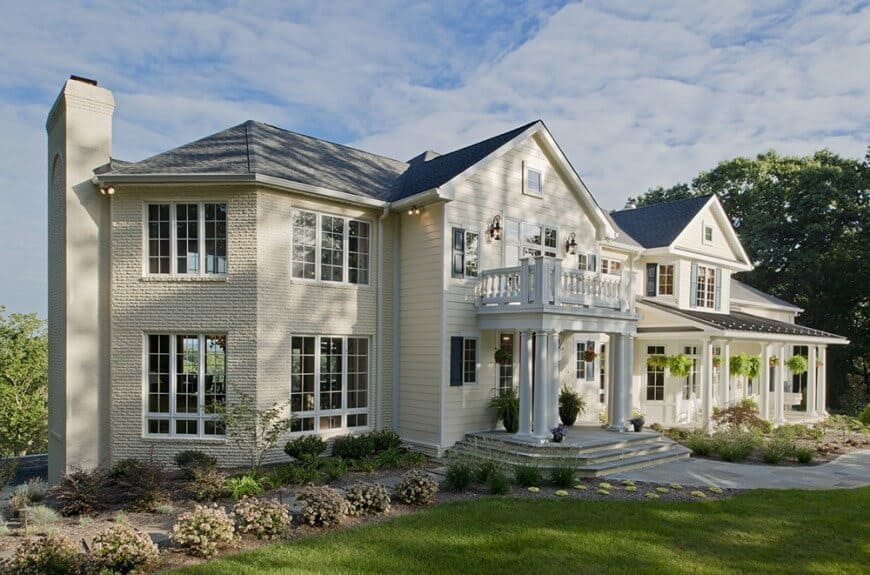 A mansion boasting a fancy exterior. The home offers a lovely driveway and a beautiful lawns and gardens.