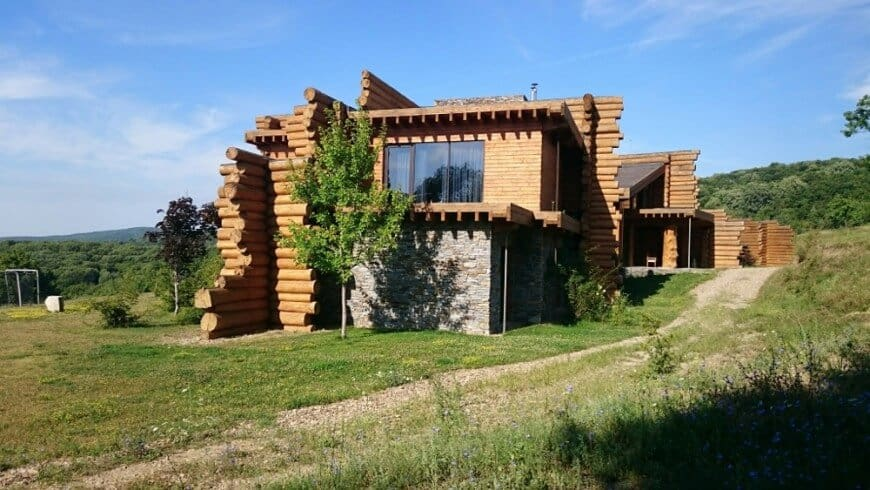 This house boasts logs exteriors and glass windows. The property has a driveway surrounded by lawn areas.