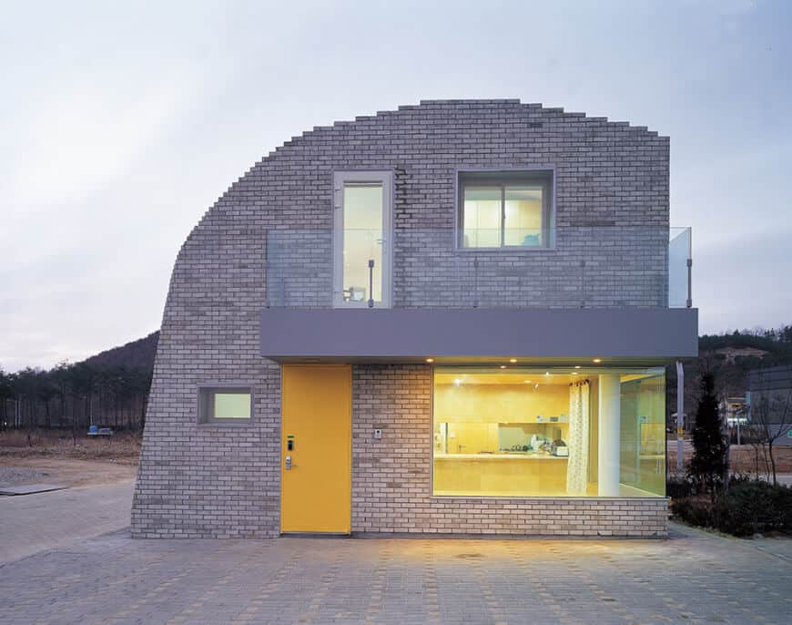 A modern house with a concrete exterior. It offers a balcony with a glass railing. The home also has glass windows.