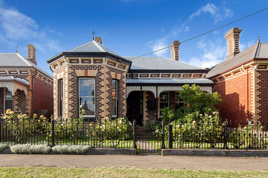 This house boasts a stunning exterior design along with a lovely garden area protected by a gated iron fence.