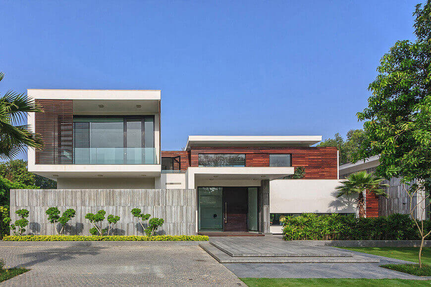 Contemporary house with a striking exterior and fence. It offers a wide backyard with gardens and lawn areas.