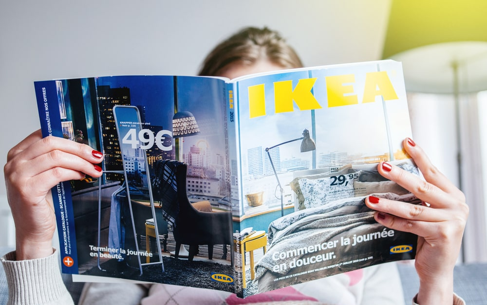 Woman reading an IKEA catalog.