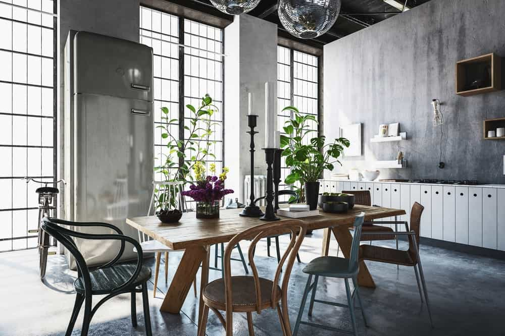 Natural light from the full height glazing contrasts the dark tones of this industrial dining room. It boasts mismatched chairs and a wooden dining table topped with tall candle holders and fresh potted plants.