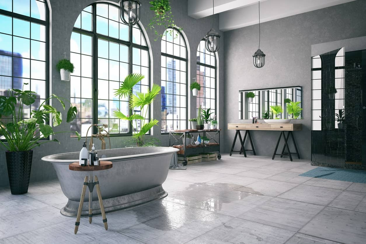 Spacious industrial style primary bathroom with an elegant freestanding tub and a very attractive walk-in shower. The room features multiple indoor plants as well.