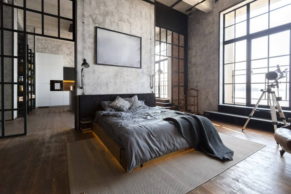 This primary bedroom is framed with black aluminum that matches the large window allowing an abundance of natural light in. It showcases a tripod floor lamp and a cozy platform bed accented with warm lighting underneath.