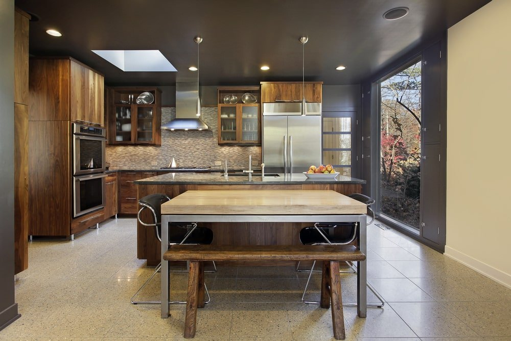 This Industrial-style dine-in kitchen has matte gray walls and ceiling with recessed lights and a skylight over the cooking area at the L-shaped structure of the wall. This structure matches with the wooden kitchen island beside the dining table that matches well with the gray floor tiles.