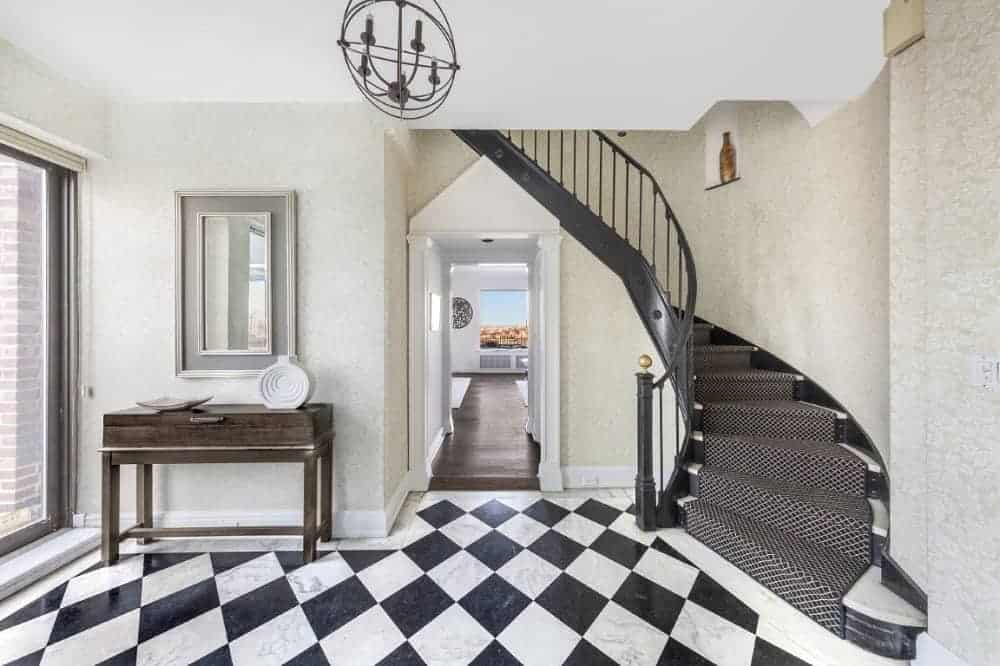 This foyer features checker tiles flooring and a staircase with carpeted steps.
