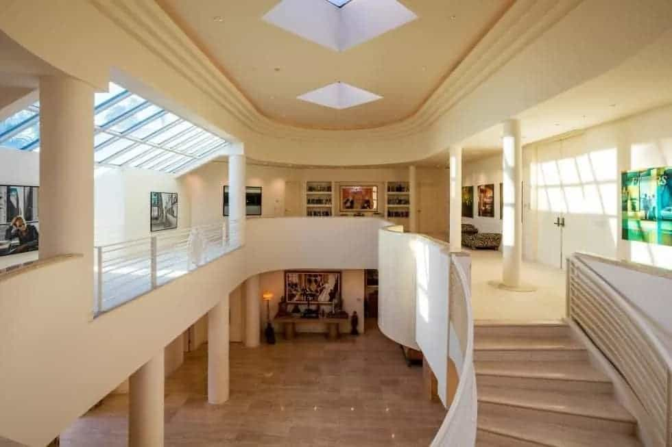 This is a view of the mansion foyer from the second level indoor balcony. The area has a tall beige ceiling with skylights that brighten the beige walls.