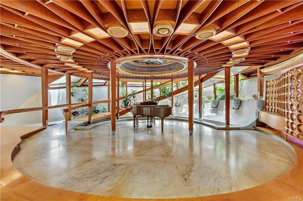 A grand entry foyer boasting a stunning custom ceiling along with a grand piano in the middle.