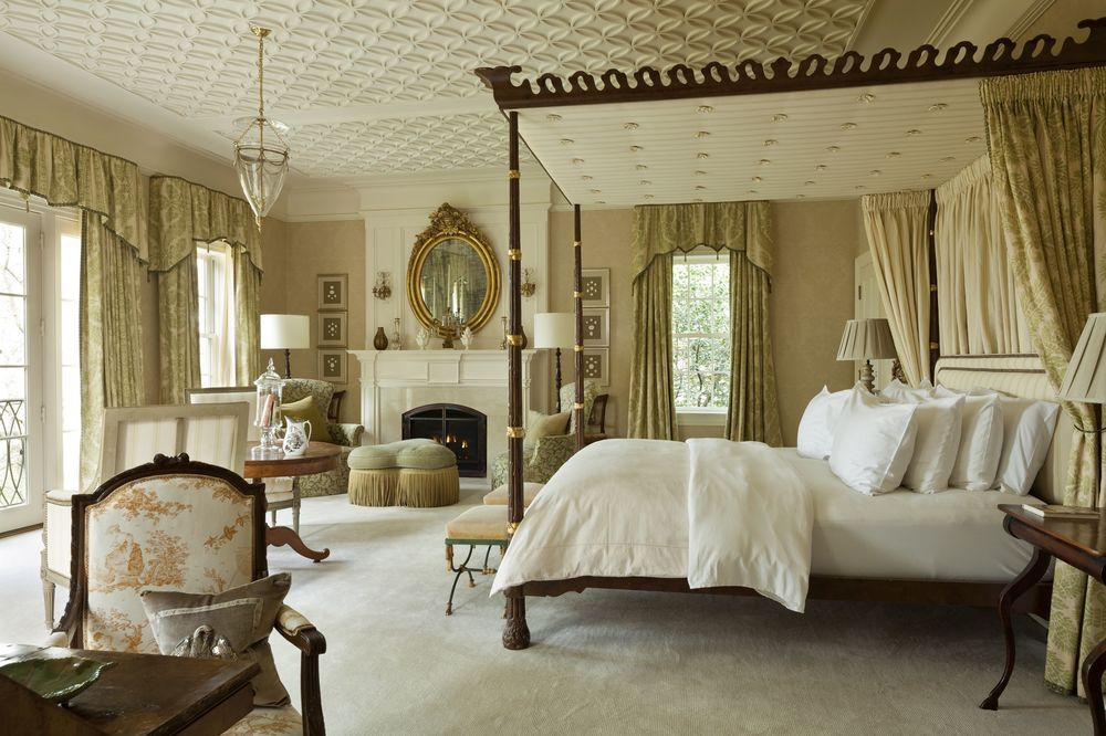 The primary bedroom has a beautiful four-poster bed and a charming patterned beige ceiling that matches with the walls and the fireplace mantle.