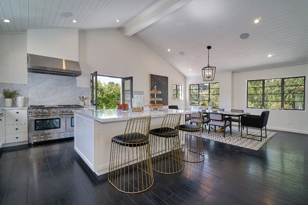 A spacious kitchen featuring a stylish marble countertop and backsplash. There's a large center island as well, with space for a breakfast bar.