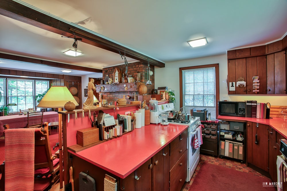 This is the kitchen with a wooden kitchen island that has red countertops making it stand out against the light tone of the walls and ceiling.