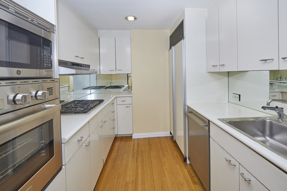 The long and narrow kitchen has white shaker cabinets lining the walls that make the stainless steel appliances stand out.