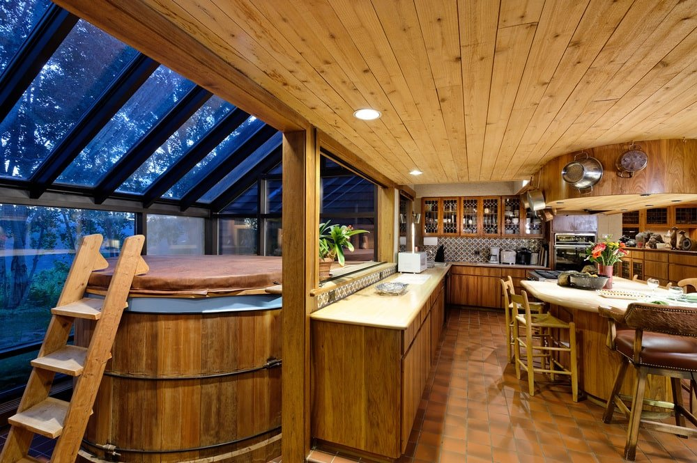 The spacious kitchen has wooden cabinetry that matches the ceiling. It also has a kitchen island and an L-shaped peninsula with wooden pillars and attached to a wooden hot tub.
