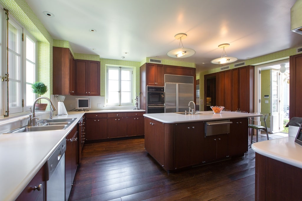 The kitchen has a kitchen island in the middle of the hardwood flooring. This blends well with the dark wooden tone of the cabinetry contrasted by the white countertops.