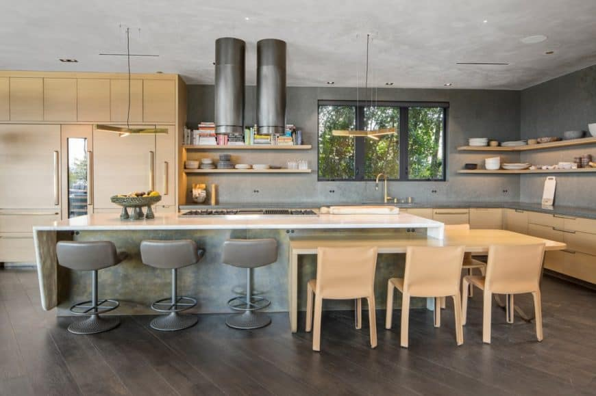 The kitchen has a gray and wooden tone to its elements. The large gray kitchen island has an attached wooden table on one end paired with chairs that stand out against the dark hardwood flooring.