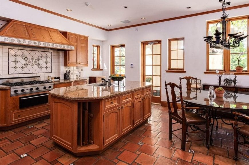 This eat-in kitchen has terracotta flooring tiles that go well with the wooden cabinetry of the kitchen island and the cooking area across from it.