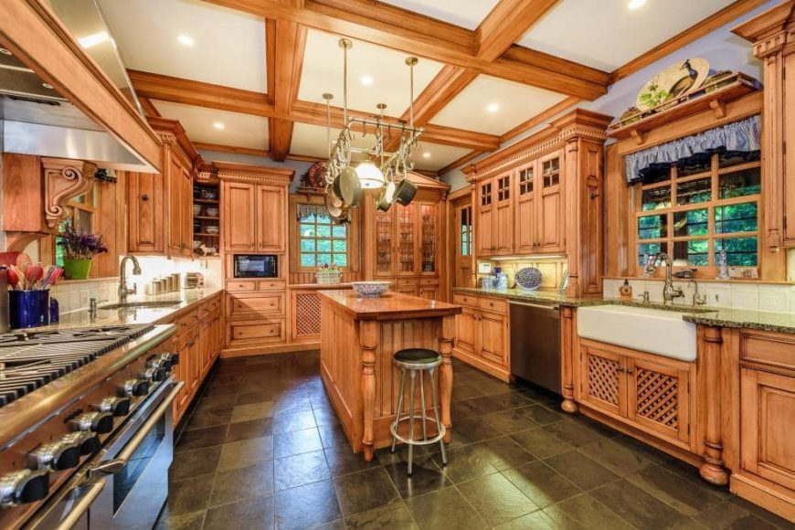 This is the kitchen that has a coffered ceiling to match the wooden cabinetry lining the walls as well as the narrow kitchen island.