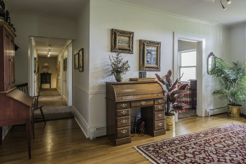 This foyer has a wooden credenza on the side that matches well with the hardwood flooring that is topped with a patterned area rug. These stand out against the bright beige walls and ceiling.