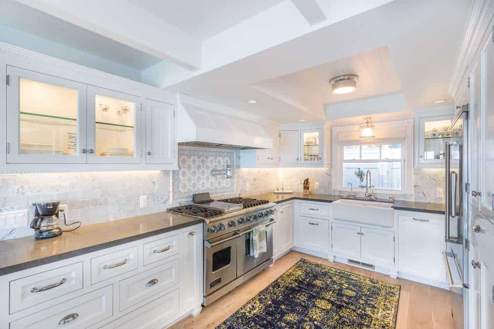 The kitchen of the house has the same white walls and ceiling to pair with the white cabinetry lining the walls that houses the stainless steel cooking area that stands out as well as the dark patterned area rug on the light hardwood flooring.