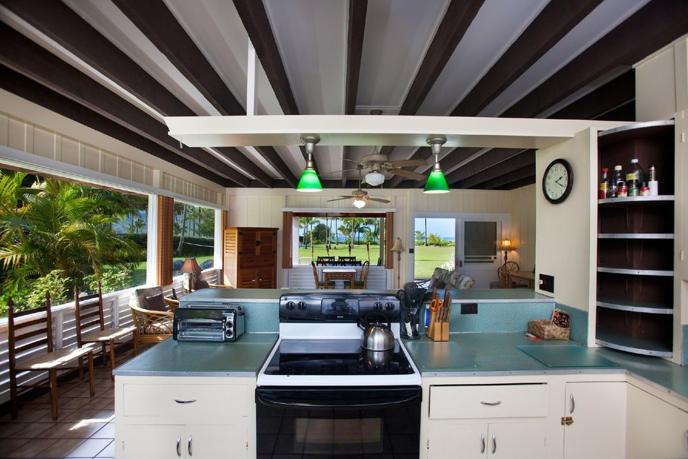 This is a look at the kitchen with lots of natural light coming in from wide windows. This complements the bright beige cabinetry of the peninsula.