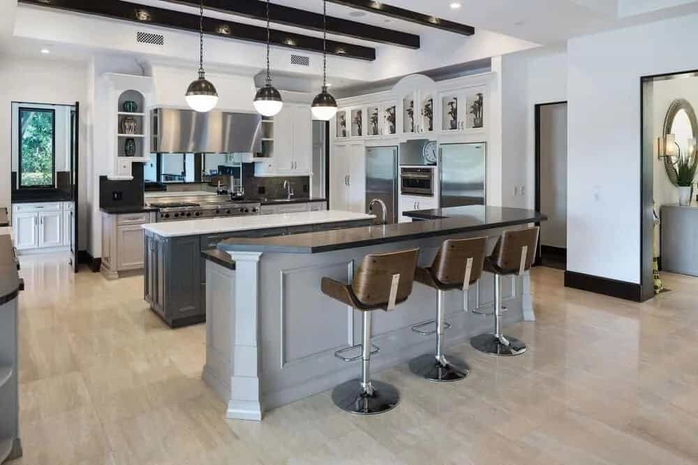This is the massive chef's kitchen with enough space for two kitchen islands. One of these is paired with stools for a breakfast bar and the other is topped with pendant lights from the beamed ceiling.