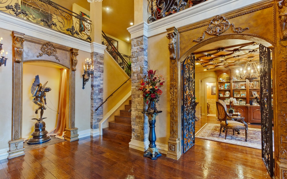 This entry foyer boasts elegant walls, hardwood floors and a tall ceiling with warm lighting.