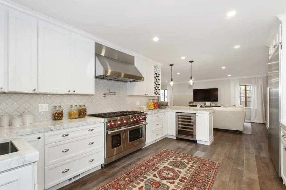 This is the bright kitchen with white cabinetry that blends with the walls and ceiling. These make the stainless steel appliances stand out as well as the hardwood flooring.