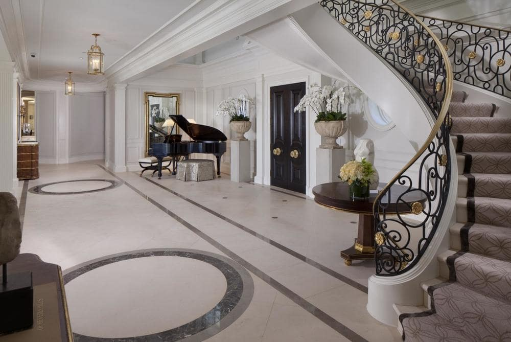 This is a look at the foyer with a dark pair of main doors that stand out against the white walls along with the black grand piano on the side.