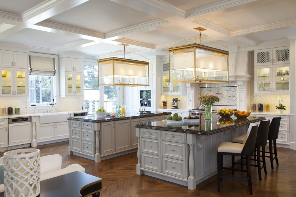 The kitchen has two large kitchen islands that has a light gray tone to its cabinetry. This stands out against the dark hardwood flooring that is topped with a bright white coffered ceiling.