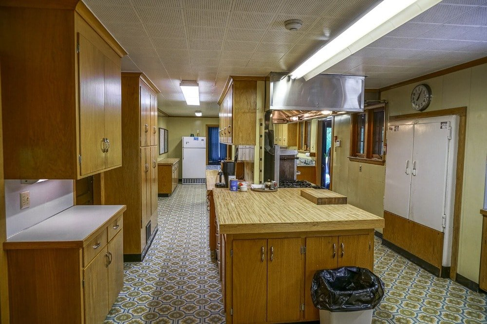 This is the large kitchen with charming wood cabinetry that pairs quite well with the patterned flooring tiles that contrast the bright beige ceiling.