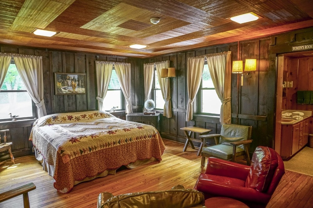 A bedroom suite featuring a cozy bed set and a personal bathroom. It has a wooden ceiling to match the hardwood flooring that is adorned with various chairs.