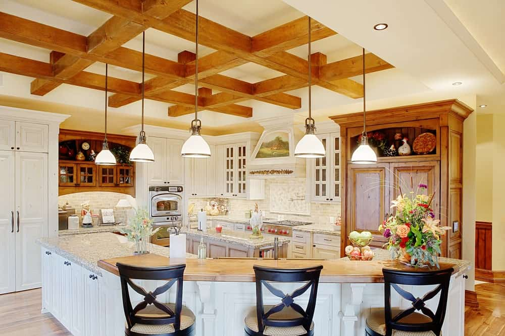 The exposed wooden beams of the beige ceiling form a checkered pattern that serves as a complex background and contrast for the classic white shaker cabinets and drawers of the kitchen islands and surrounding cabinetry that seem to glow brighter complemented by the beige walls and ceiling.