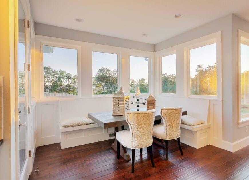 This is a brilliant kitchen dining nook with an L-shaped wooden built-in bench that blends in with the white wooden wall below the row of windows. This brings in an abundance of natural lighting for the dark wooden dining table and the redwood flooring.