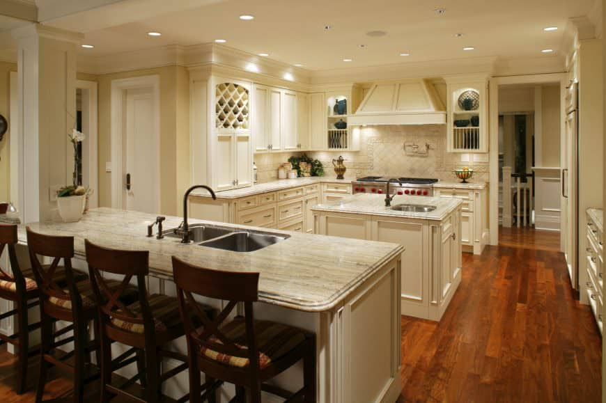 This elegant and charming kitchen has both a kitchen island and a peninsula. The island stands out against the the redwood flooring with its light beige hue matching with the rest of the cabinetry. The peninsula has a breakfast bar paired with dark wooden stools.