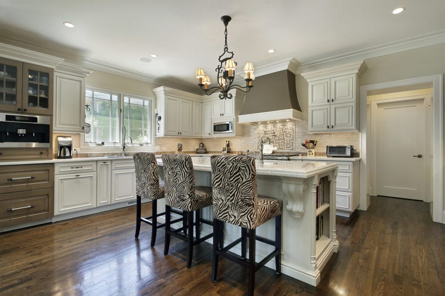 The simple yet elegant wrought iron chandelier of this kitchen stands out against the white ceiling and light beige walls. This goes well with the white shaker cabinets and drawers of the L-shaped cabinetry with a beige lit backsplash for a unique aesthetic complemented by the dark hardwood flooring.