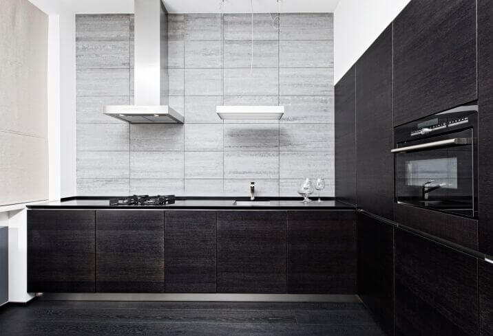 This is a simple two-toned L-shaped kitchen with charcoal black kitchen cabinets paired with black granite countertops. This matches well with the dark hardwood flooring and contrasted by the light gray walls and bright white ceiling.