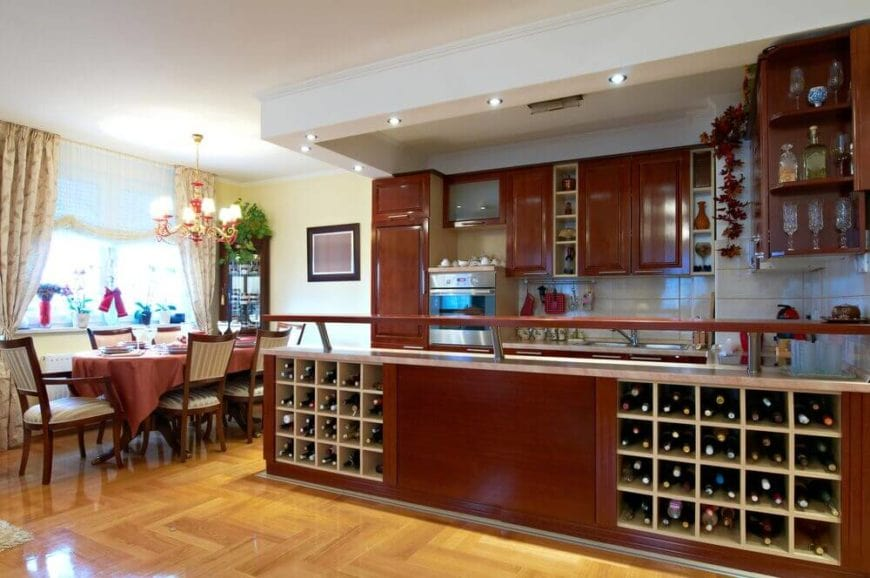 This is an elegant galley kitchen with a dining area beside it by the window. This dining set has a long dining table paired with dining chairs of the same dark wooden tone as the U-shaped peninsula of the kitchen with a built-in pair of wine storage.