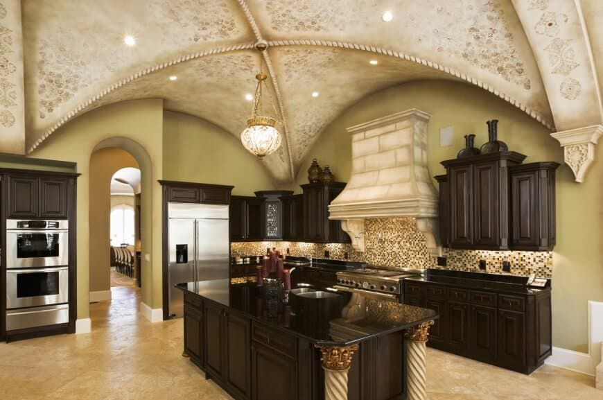 Luxury kitchen with stainless steel appliances and dark wood cabinetry matching with the central island supported by elegant spiral columns. It is illuminated by a brass pendant and recessed lights mounted on the groin vault ceiling designed with intricate details.