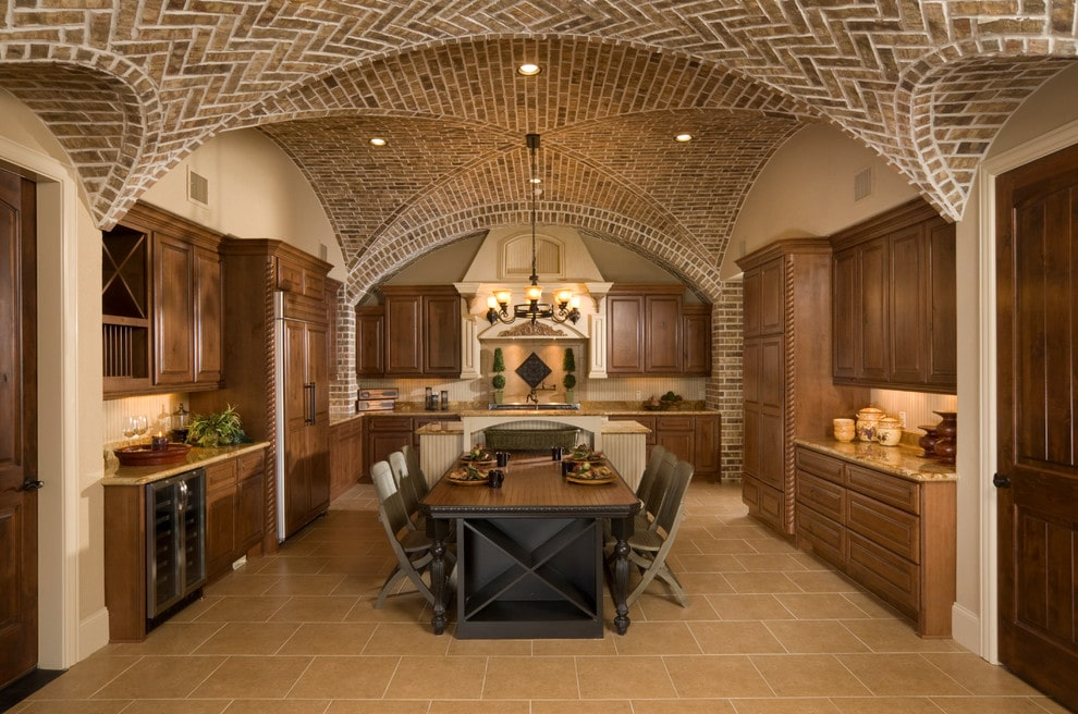 A stunning groin vault ceiling adds character in this kitchen with natural wood cabinetry and a cream vent hood that matches the beadboard island attached with a dark wood table.