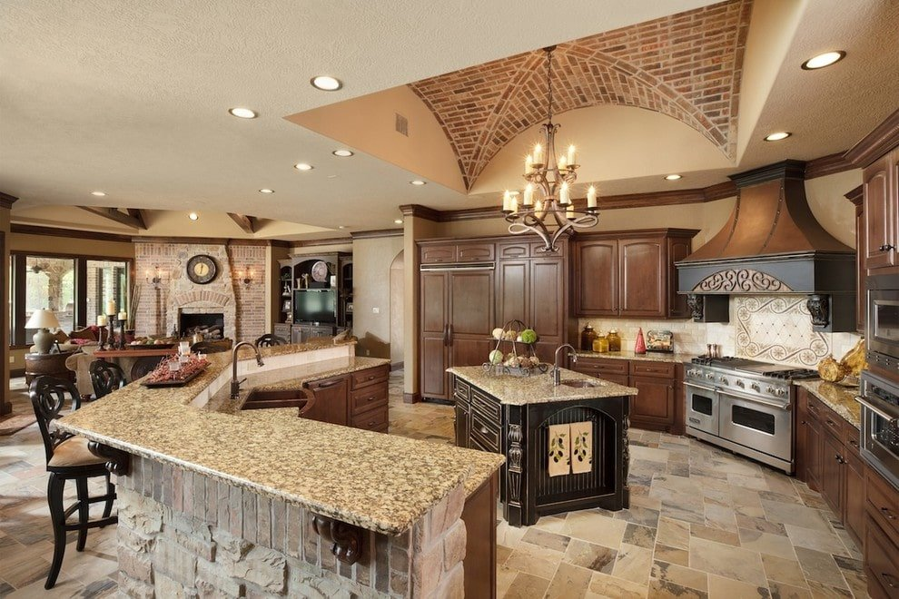 This kitchen showcases wooden cabinetry and a granite top island along with a curved peninsula that's paired with cushioned counter chairs. It has gorgeous limestone flooring and a combination of tray and groin vault ceiling clad in bricks.