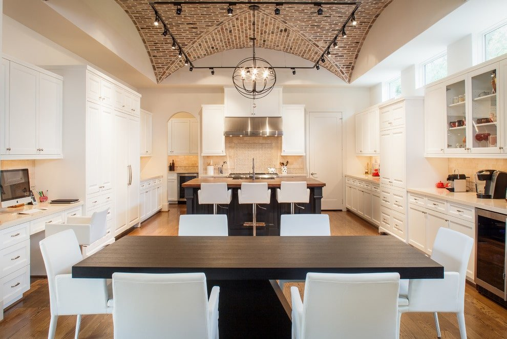 Wooden top island and a black dining table create a striking contrast to the white chairs and cabinets that blend in with the walls. It is lighted by a spherical pendant along with surrounding track lights that are fixed on the groin vault ceiling.