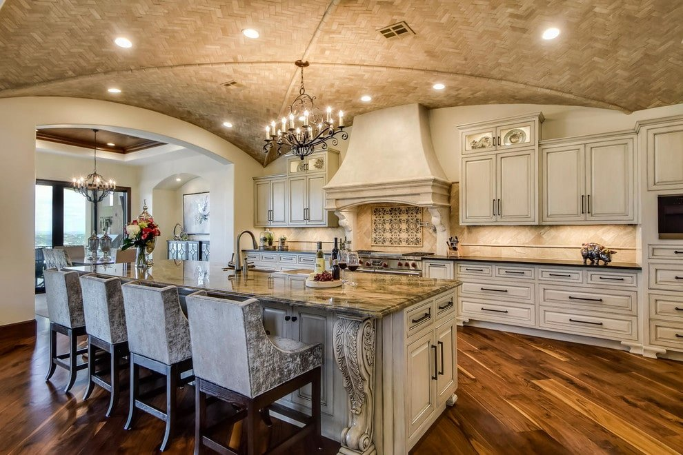 Granite top island lined with velvet wingback chairs faces the cream cabinetry and a matching vent hood that blends in with the walls. It is illuminated by recessed lights and a classic candle chandelier that hung from the groin vault ceiling clad in herringbone tiles.