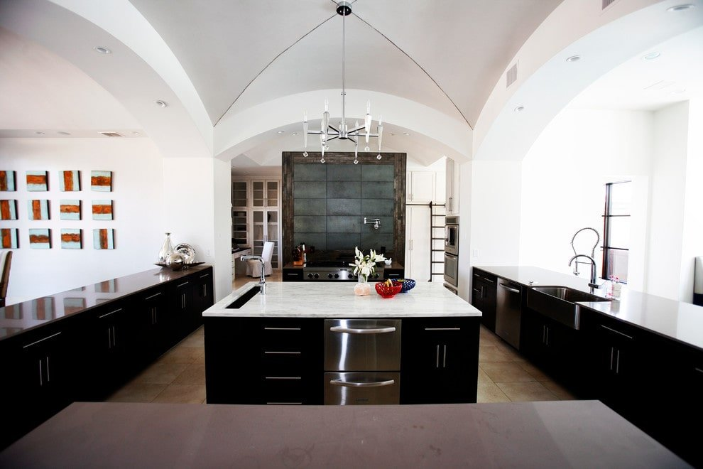 Contemporary kitchen with white walls and groin vault ceiling contrasted by black cabinets and a marble top island. It is equipped with stainless steel appliances and a farmhouse sink paired with chrome fixtures.