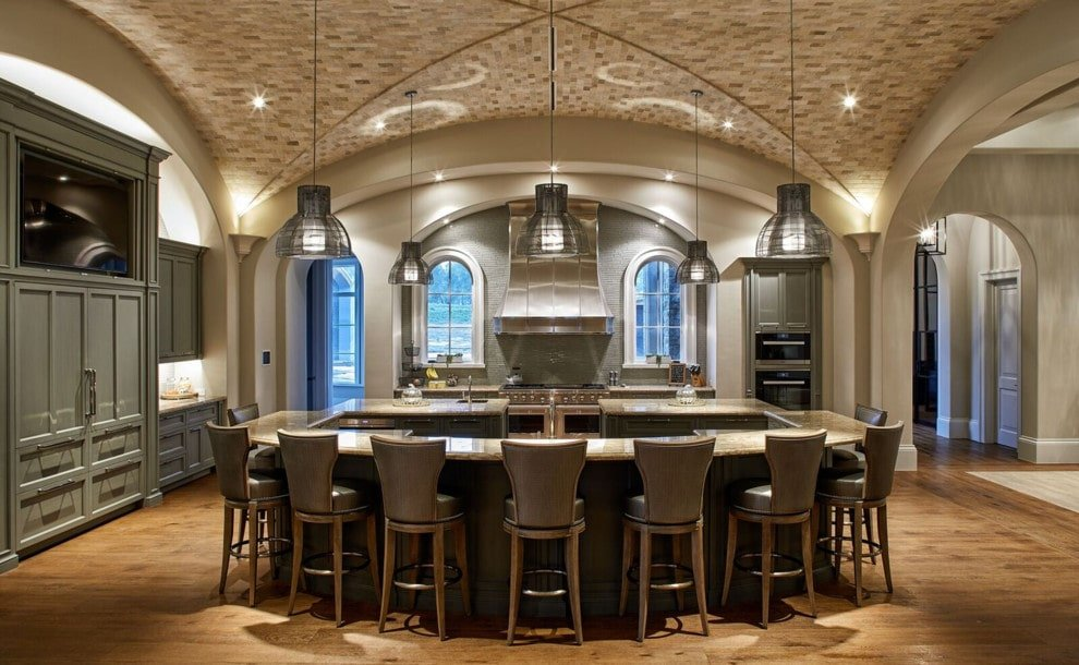 Gray wingback chairs sit at an immense central island illuminated by lovely dome pendants. It is surrounded by open archways along with gray cabinets and inset appliances.