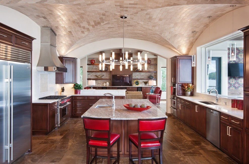 Round chandelier with linear lamps illuminates the granite top island that's complemented with red cushioned chairs over concrete tiled flooring. It is accompanied by wooden cabinetry and a picture window that allows natural light in.