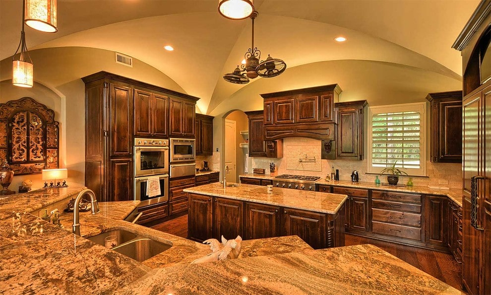 The warm kitchen offers stainless steel appliances and natural wood cabinetry matching with the center island that's lighted by a vintage pendant. It includes a curved two-tier peninsula that's topped with granite countertops and a dual sink paired with gooseneck faucet.