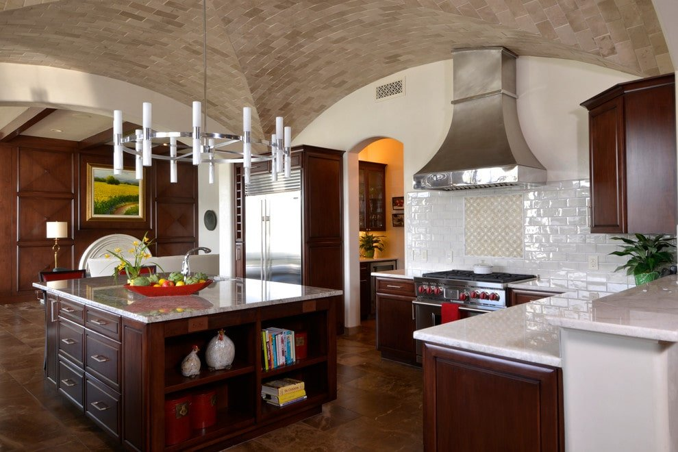 A contemporary chandelier illuminates the granite top island that's fitted with built-in drawers and open shelving. It is accompanied by dark wood cabinetry along with stainless steel appliances and vent hood fixed above the white subway tile backsplash.