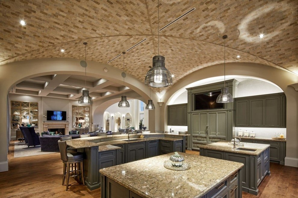 An expansive kitchen enclosed in open archways and a stunning groin vault ceiling mounted with lovely dome pendants. It showcases gray cabinets and three islands all topped with matching granite countertops.